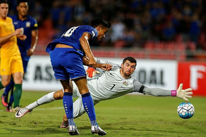 Teerasil Dangda scoring past Australia goalkeeper Mathew Ryan to put Thailand level 1-1 at the Rajamangala National Stadium in Bangkok. The 2-2 result means the Socceroos fall out of the automatic qualifying spots.