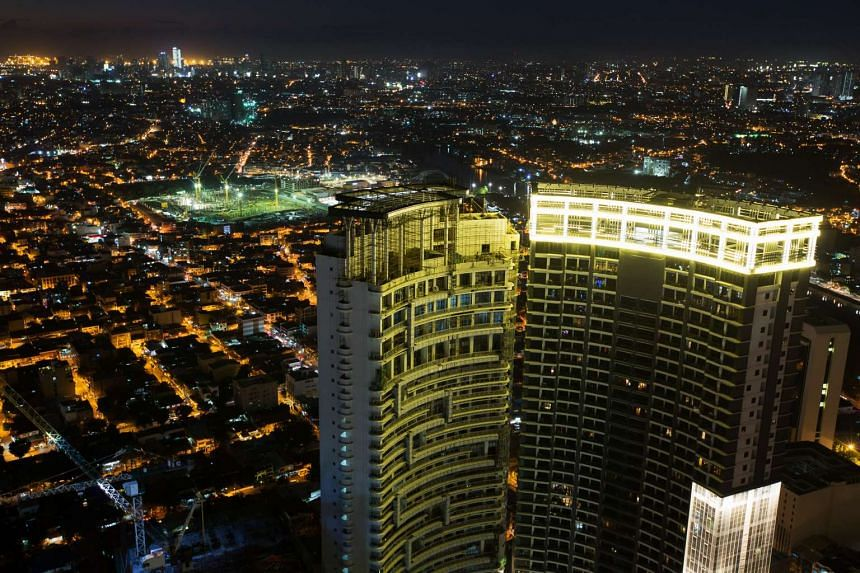 A residential building under construction at night in the Makati district of Manila.