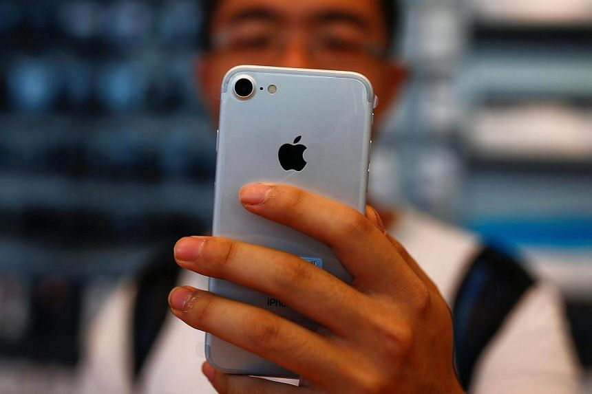 A man holds his new iPhone 7 at an Apple store in Beijing, China on Sept 16, 2016.