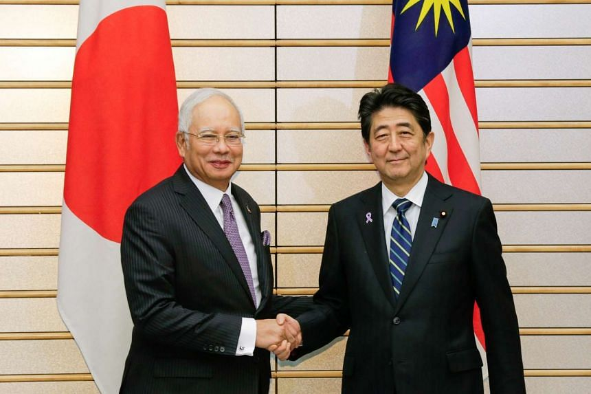 Malaysian Prime Minister Najib Razak (left) shakes hands with Japanese Prime Minister Shinzo Abe at the start of their meeting at Abe's official residence in Tokyo on Nov 16, 2016.