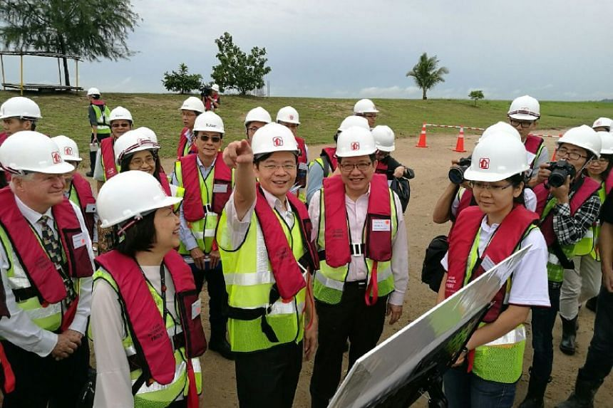 National Development Minister Lawrence Wong getting briefed on the upcoming Pulau Tekong reclamation works.