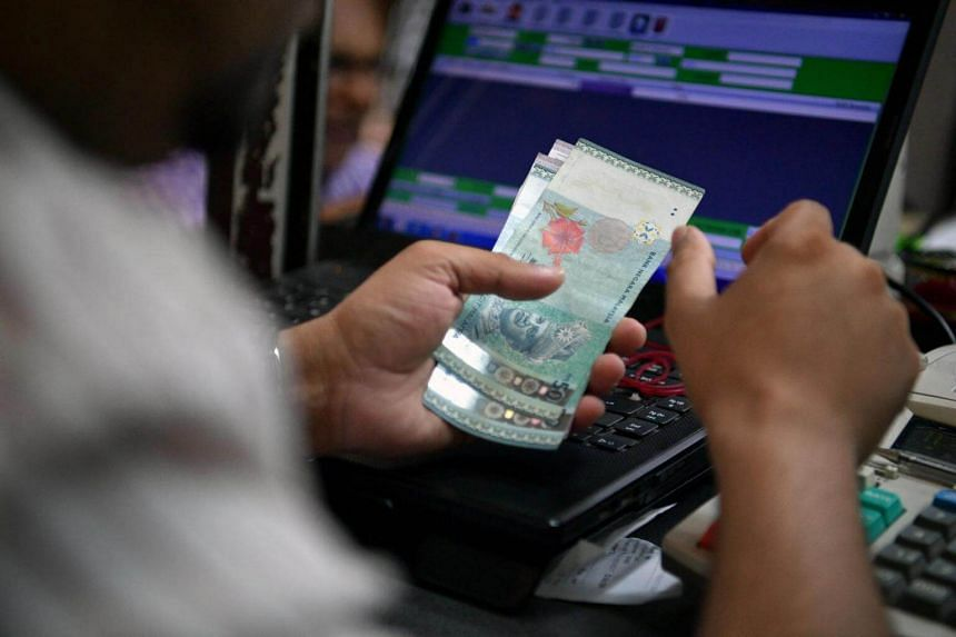 An employee counts  Malaysian Ringgit banknotes on Nov 14, 2016.
