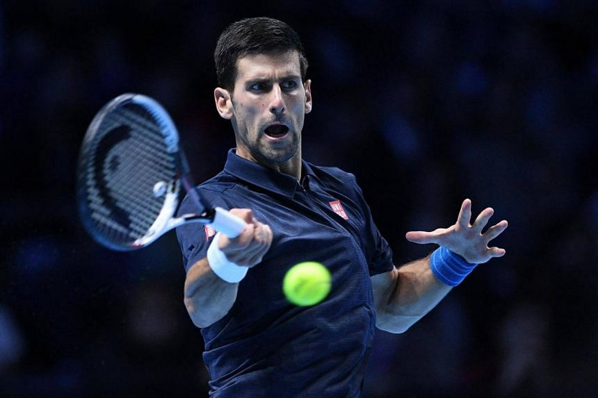 Novak Djokovic returns the ball against Milos Raonic during their match at the ATP Tour Finals.