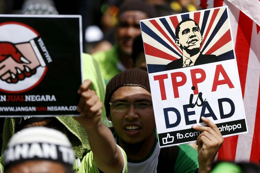 Protestors wave placards at a rally against the Trans Pacific Partnership (TPP) just days before parliament is due to open a debate on the free trade pact in Kuala Lumpur, Malaysia on Jan 23, 2016.
