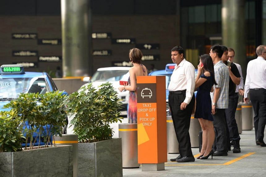 People in a taxi queue at Marina Bay Financial Centre.