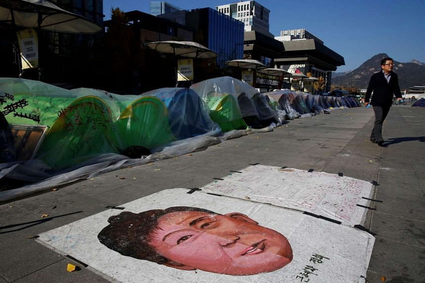 Above: A painting of Ms Park is pasted on the ground in front of tents put up by protesters calling for her resignation in central Seoul yesterday.