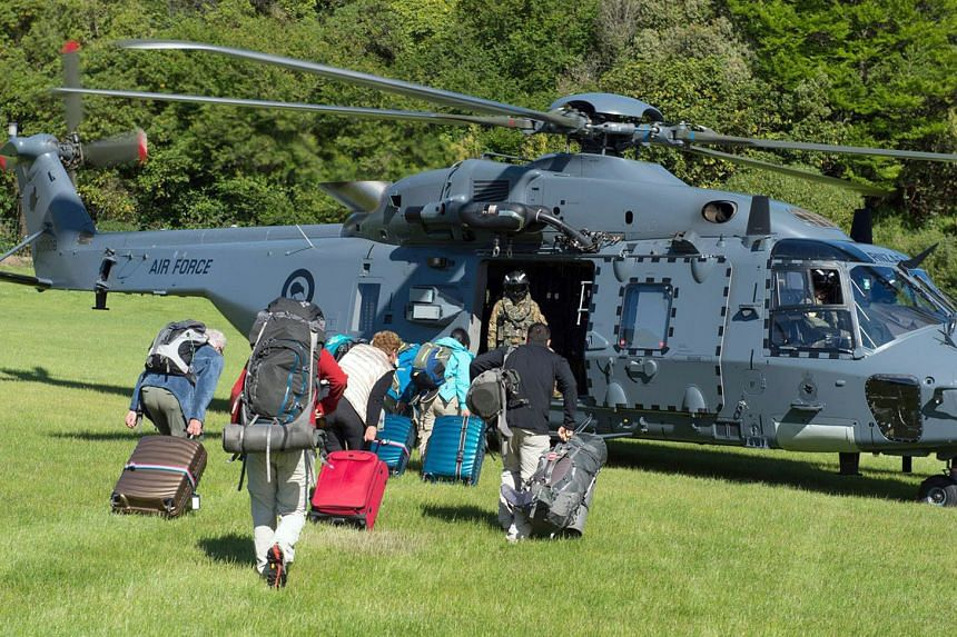Some of the 1,200 tourists stranded by the earthquake in Kaikoura being evacuated by a New Zealand Defence Force helicopter yesterday. Due to the quake, huge landslides have cut road and rail links to the town, where police say water is running low, power