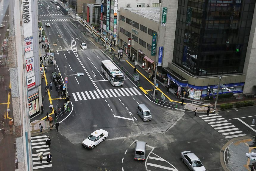 The giant sinkhole which appeared on a five-lane street in the Japanese city of Fukuoka last week has been filled in, and the repaired street (above) reopened to the public yesterday.