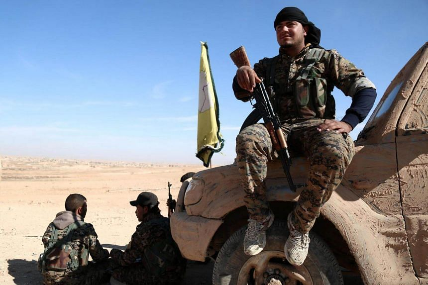 A Syrian Democratic Forces (SDF) fighter rests with his weapon on a vehicle camouflaged with mud, north of Raqqa.
