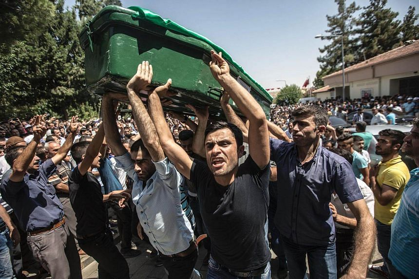People carry a coffin during a funeral for victims of an attack on a wedding party that left 50 dead in Gaziantep in southeastern Turkey near the Syrian border on Aug 21, 2016.