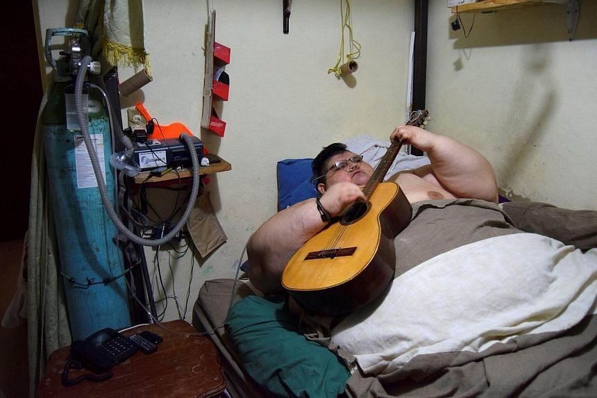 Juan Pedro, plays a guitar as he waits for paramedics to transport him to a hospital in Guadalajara in Aguascalientes, Mexico on Nov 15, 2016.