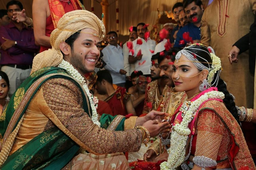 Bramhani (right), daughter of Gali Janardhan Reddy, sits with her groom, Rajeev Reddy during their wedding at the Bangalore Palace Grounds in Bangalore.