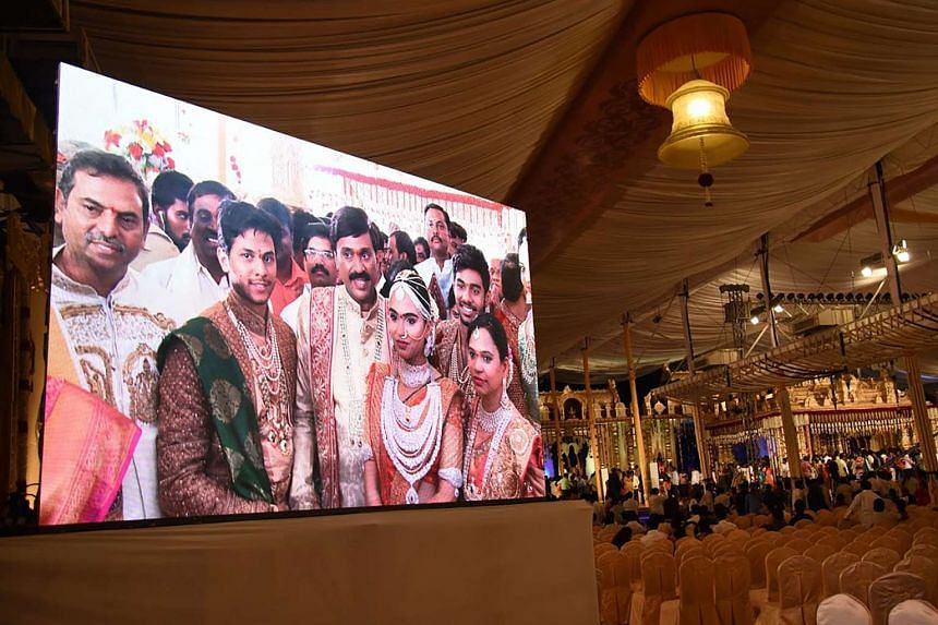 Indian mining tycoon, Gali Janardhan Reddy, (centre) is seen on a big screen as he poses with his daughter Brahmani (second from right) and son-in-law, Rajeev Reddy (second from left) during their wedding at the Bangalore Palace Grounds in Bangalore.