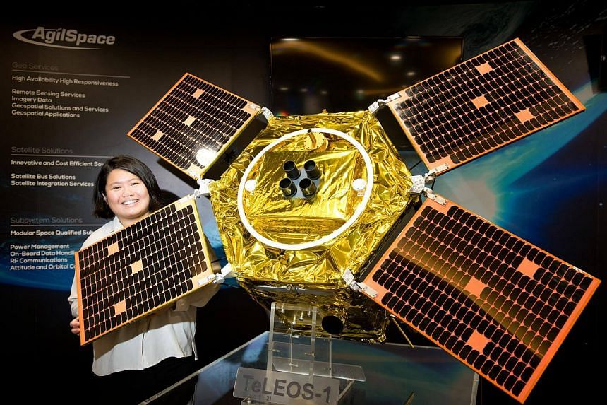 Ms Grace Parn, senior engineer in the Structural and Mechanical department with ST Electronics (Satellite Systems) poses with a model of the TeLEOS-1 satellite.