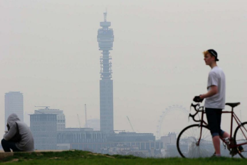 A cyclist takes a break at the top of Primrose Hill in London as the city below lies shrouded in pollution.