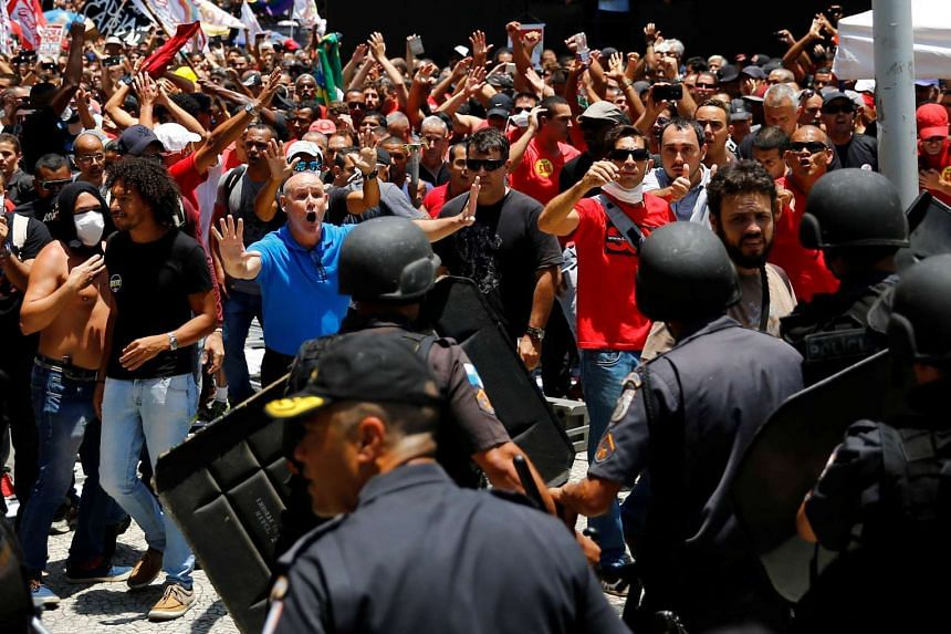 Civil servants clash with riot police during a protest against the Rio de Janeiro state government and a plan that will limit public spending.