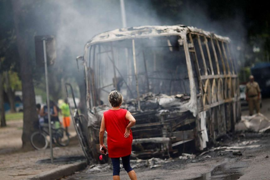 A woman looks at a burned bus near a protest against the Rio de Janeiro state government and a plan that will limit public spending.