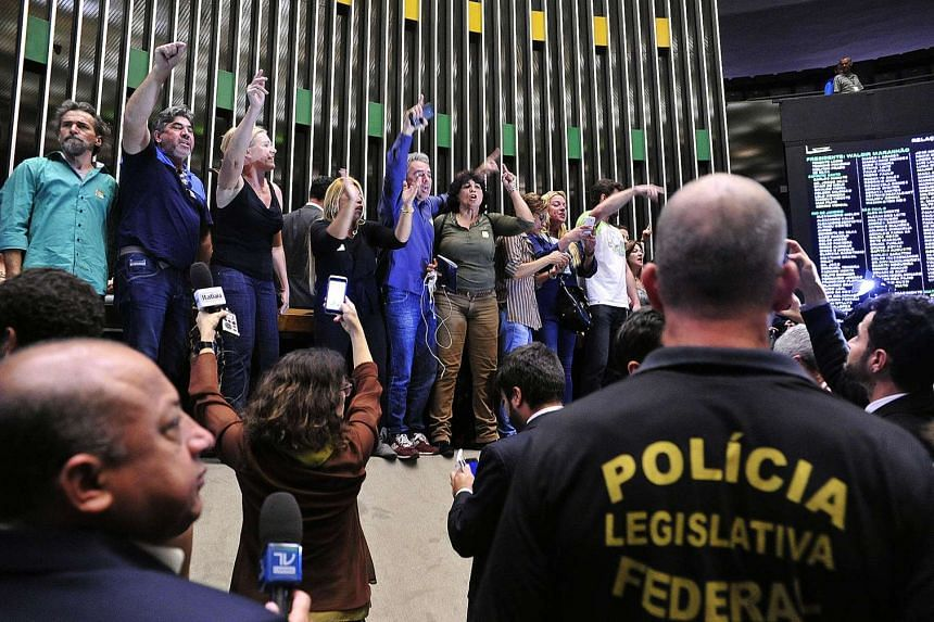 Demonstrators in favor of a military intervention in Brazil invade the lower house plenary session in Brasilia on Nov 16, 2016.