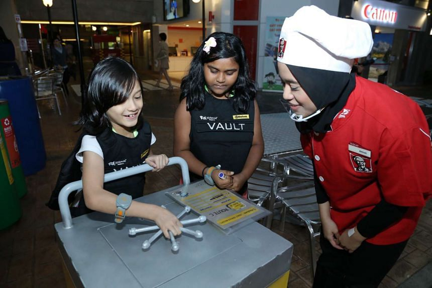 Elie Nur Aisha Bte Johari, 8 (left), and Arun Thirral Amiltham Alarmugill, 7, try their hands at being Maybank Cash Officers at KidZania Singapore during an exclusive after-hours party supported by The Straits Times School Pocket Money Fund.