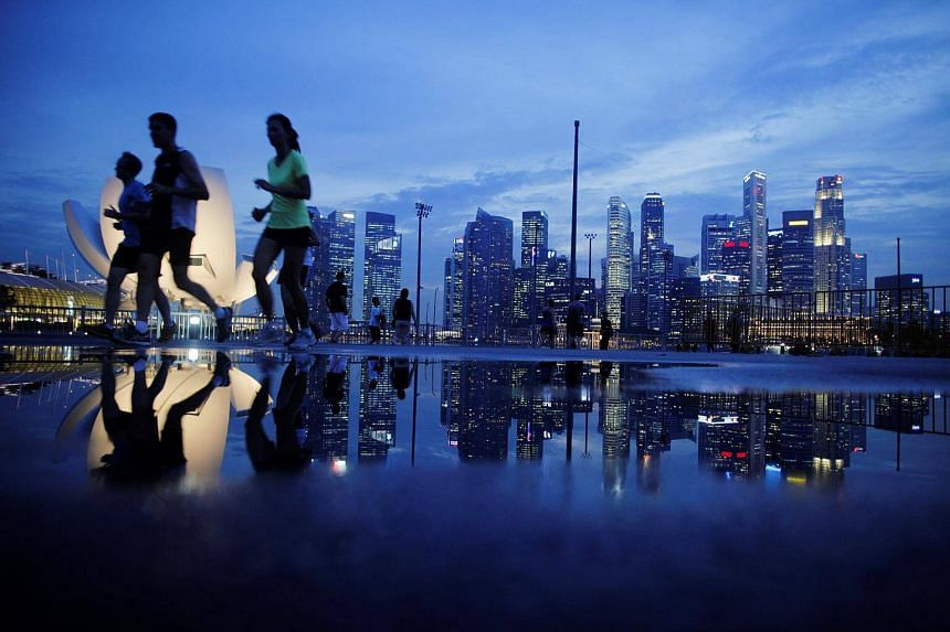 Joggers run past as the skyline of Singapore's financial district is seen in the background.