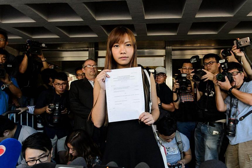 Pro-independence lawmaker Yau Wai-ching (centre) holds a court ruling as she leaves the High Court in Hong Kong on Nov 15, 2016.
