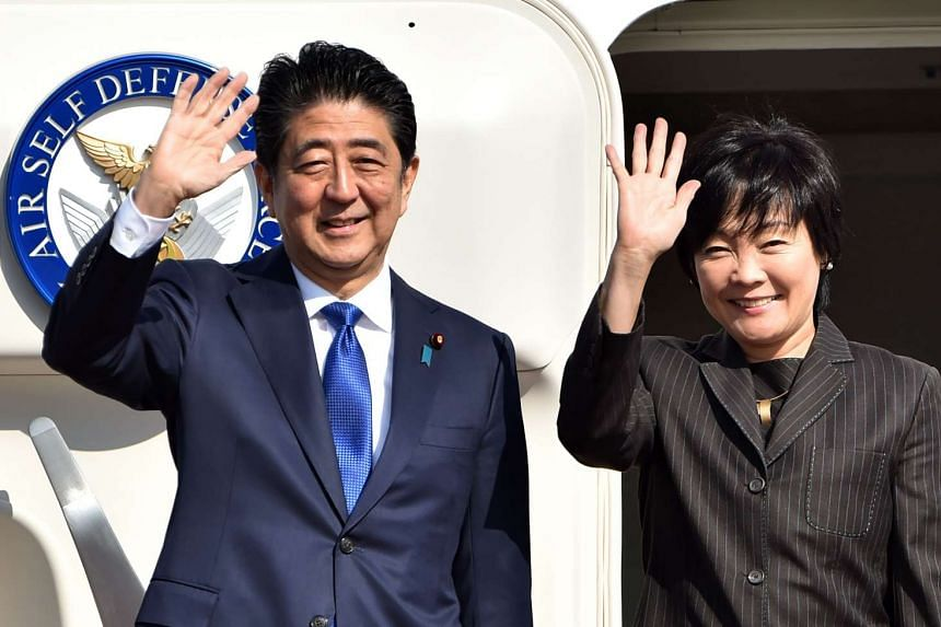 Japan's Prime Minister Shinzo Abe and his wife Akie wave to well-wishers prior to boarding a government plane at Tokyo's Haneda on Nov 17,2016.