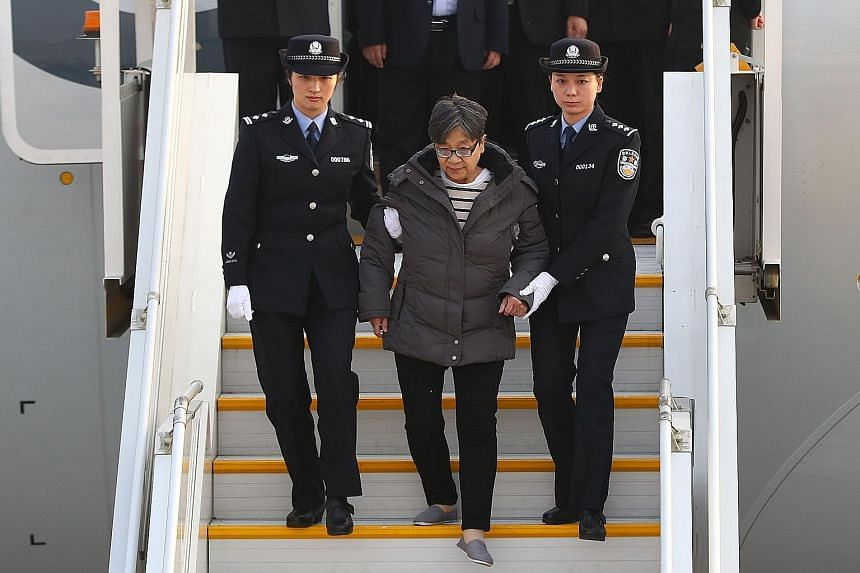 Ms Yang Xiuzhu disembarking from a plane in Beijing after returning from the US yesterday. She had fled China in 2003 after the authorities began investigating her alleged involvement in criminal activities.