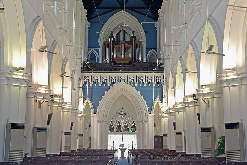 From the inside of St Andrew's Cathedral, facing the back, one can see the pipe organ at the top, with stained glass panels below depicting the biblical figures Matthew, Mark, Luke and John.
