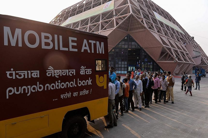 Residents of New Delhi waiting to withdraw money from a mobile ATM on Tuesday. Mr Modi's move to withdraw high-denomination notes has left people scrambling for cash. It has also affected small businesses and the informal sectors which normally rely