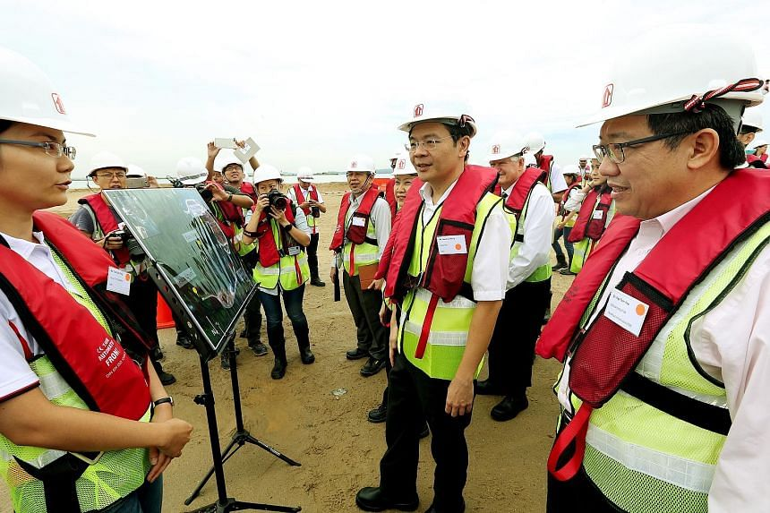 Right: National Development Minister Lawrence Wong being briefed by HDB engineer Chia Siok Teng during his site visit to Pulau Tekong yesterday. Beside him were HDB chief executive Cheong Koon Hean (partially blocked) and HDB group director (building