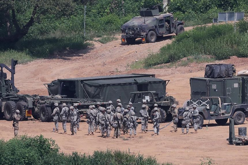 Above: American soldiers taking part in a military exercise in August near the demilitarised zone separating the two Koreas in Paju, South Korea. The US has about 28,500 soldiers in the country. Below: Two US ships docked at the White Beach Naval Fac