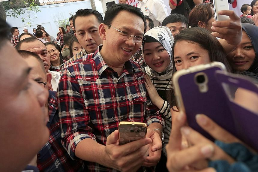 Mr Basuki taking selfies with supporters in Jakarta yesterday. The politician had been widely expected to be re-elected as Jakarta governor.