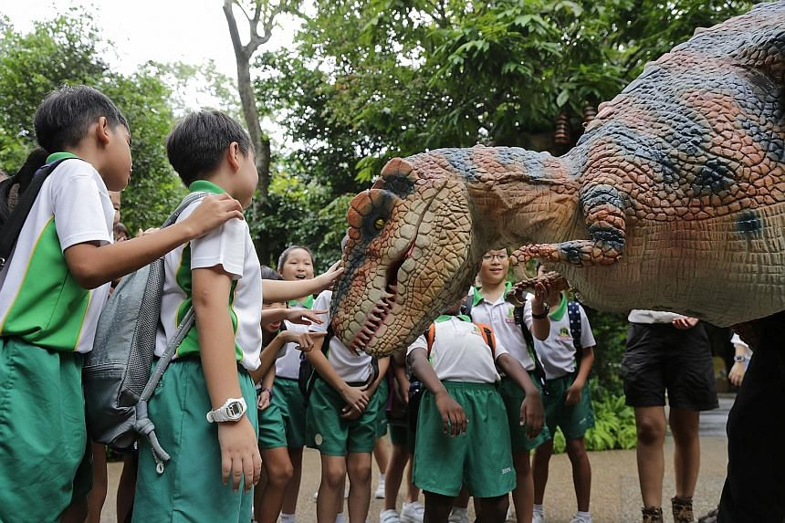 Students interacting with a T-rex mascot at the entrance to Dinosaur Valley - Singapore Zoo's latest attraction, which features lifelike animatronics of 16 dinosaur species including Tyrannosaurus rex and Spinosaurus. The exhibit seeks to raise aware