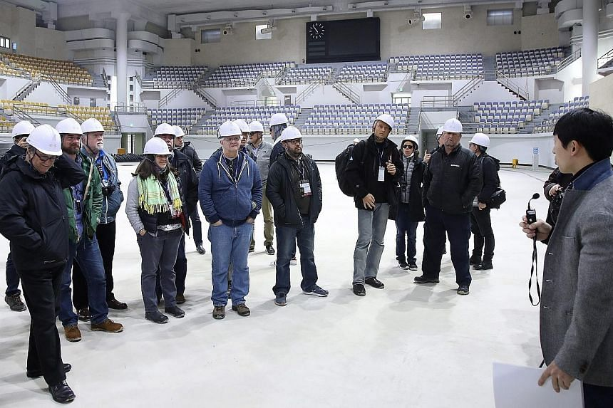 An organising committee official of the Pyeongchang Winter Olympics (right) briefing international media representatives during their visit to a curling centre under construction in the eastern port city of Gangneung, South Korea, on Nov 9. The commi