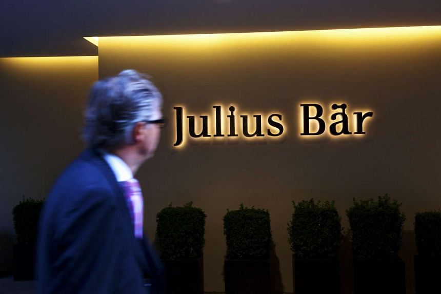 A businessman passes the headquarters of Julius Baer Group Ltd in Zurich, Switzerland.