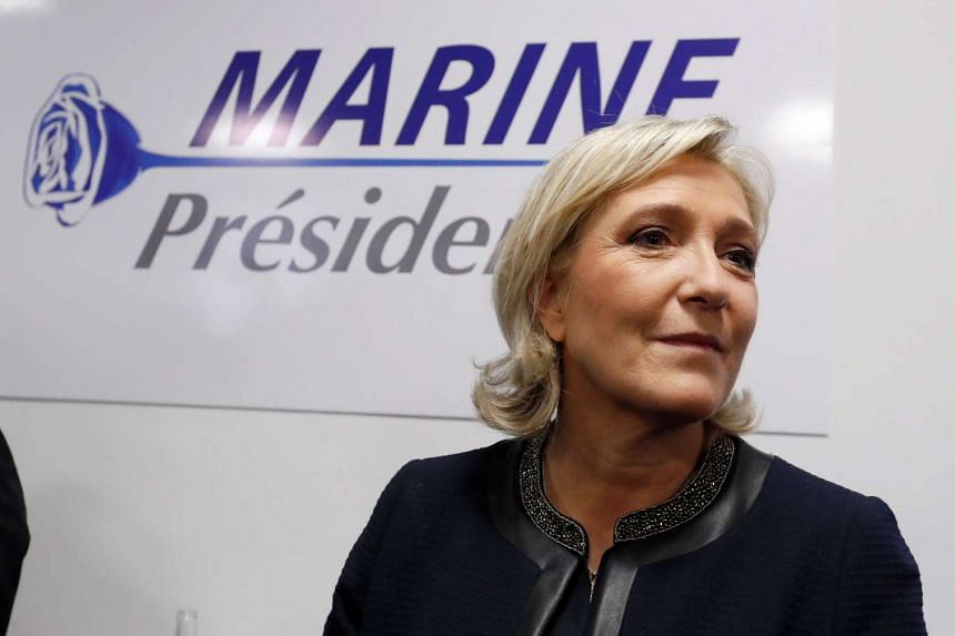 National Front leader Marine Le Pen poses in front of a poster for her 2017 French presidential election campaign.