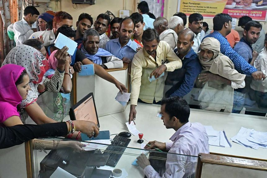Customers wait to exchange Indian 500 and 1,000 rupee banknotes at a Syndicate Bank branch in Dadri, Uttar Pradesh, on Nov 15, 2016.