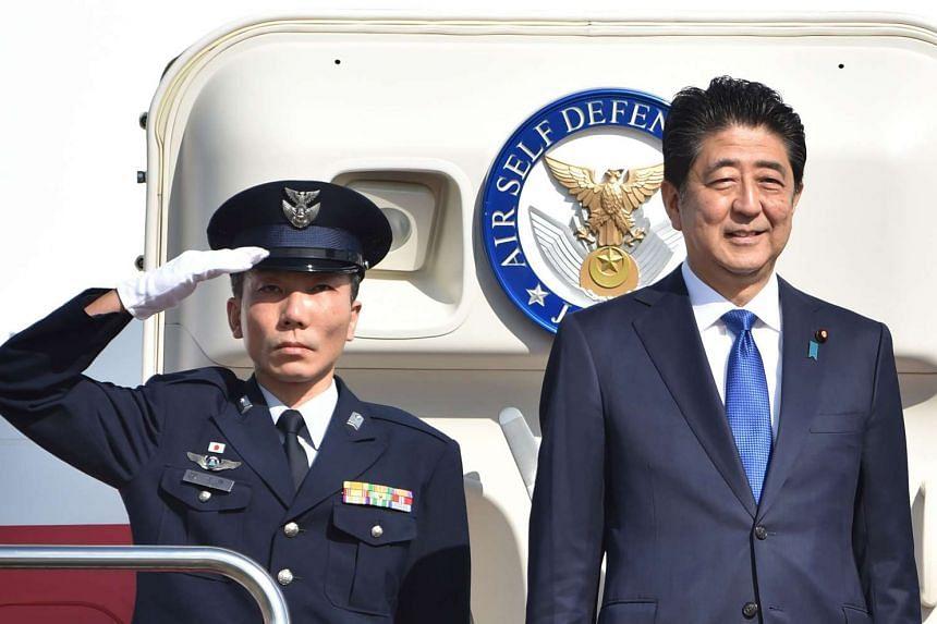 Japan's Prime Minister Shinzo Abe (right) leaves Tokyo's Haneda Airport on Nov 17, 2016.