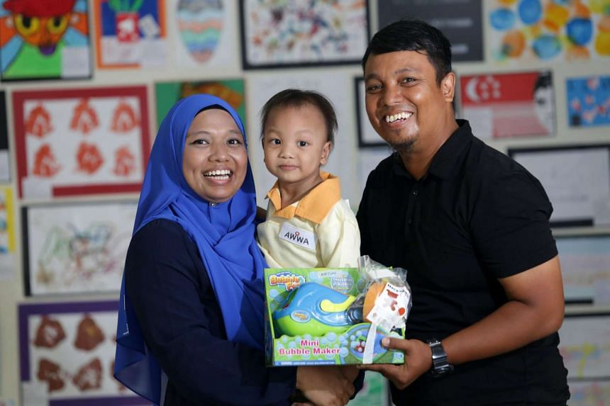 Two-year-old Mohamad Zidane Bin Mohamad Zaihiri with his parents Ms Norsuhaidah Bte Muhammad, 35 and Mr Mohamad Zaihiri Bin Mohamed Salleh, 38. He receives a bubble maker, with an attachable remote that allows him to operate the toy.