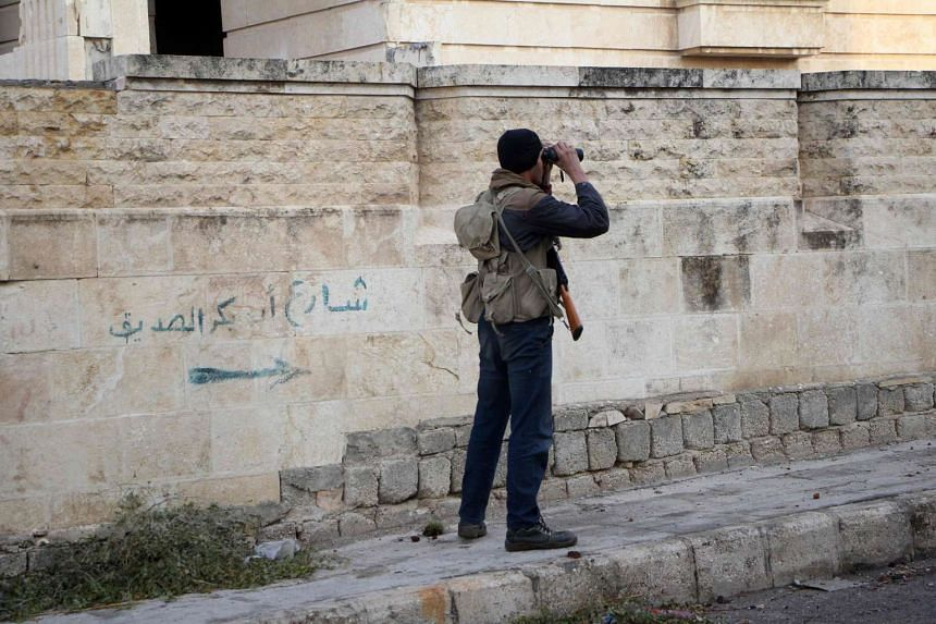 A rebel fighter from the Jaish al-Fatah brigades monitors a street with binoculars on Oct 29, 2016 in the neighbourhood of Dahiyet al-Assad, Aleppo, after rebel groups retook control of the area.