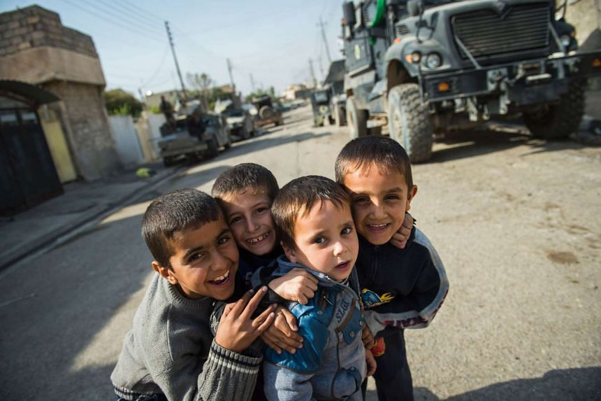 come out to play in the street as soldiers from the Iraqi Special Forces secure the streets in the Karkukli neighbourhood, Mosul, on Nov 14, 2016.