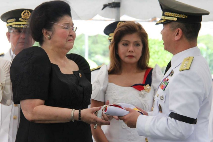 Imelda Marcos (left), the widow of late dictator Ferdinand Marcos, crying as she receives the Philippine flag from a military officer during burial rites at the Heroes' Cemetery in Pasay City, Manila.