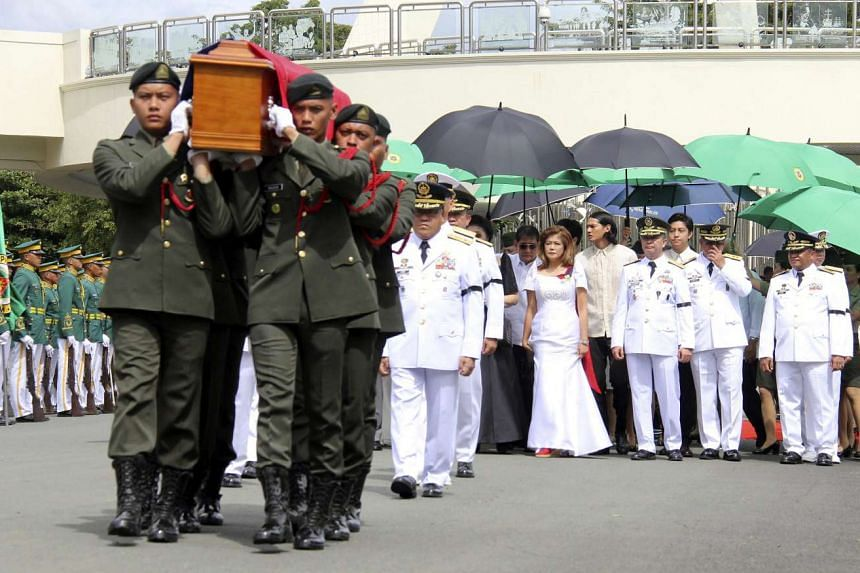 Filipino soldiers carrying the flag-draped casket of the late Philippine dictator Ferdinand Marcos during burial rites at the Heroes' Cemetery in Pasay City, Manila on Nov 18, 2016.