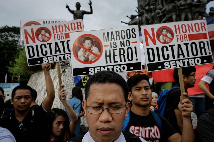 A Filipino priest (center) joins demonstrators holding placards during a protest against the burial of former dictator Ferdinand Marcos at the People Power Monument in Quezon City, northeast of Manila on Nov 18, 2016.