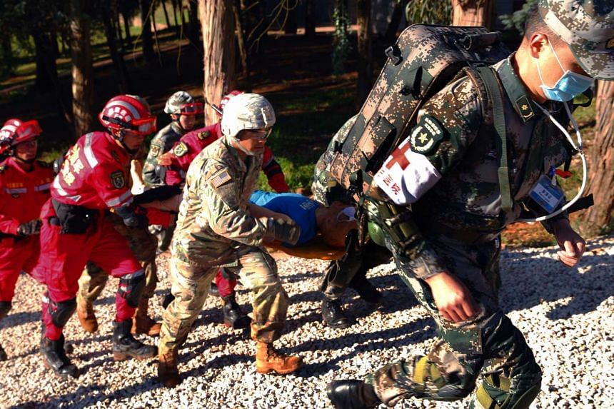 Chinese and US soldiers carry a stretcher during a joint disaster relief training session in Kunming, in China's Yunnan province on Nov 18, 2016.