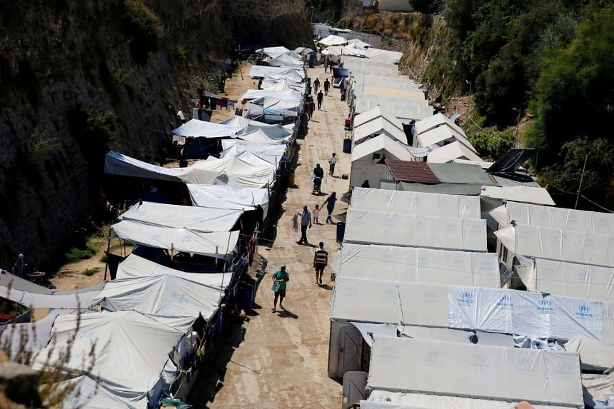 Refugees and migrants make their way at the Souda municipality-run camp, on the island of Chios, Greece, on Sept 7, 2016.