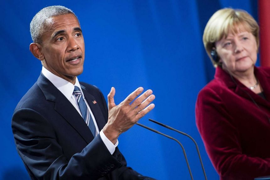 German Chancellor Angela Merkel (right) listens while US President Barack Obama speaks during a press conference after their meeting at the chancellery in Berlin on Nov 17, 2016.