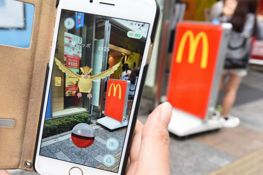 A woman plays the Nintendo's Pokemon Go game on her mobile phone in front of a McDonald's restaurant at Akihabara shopping district in Tokyo on July 22, 2016.