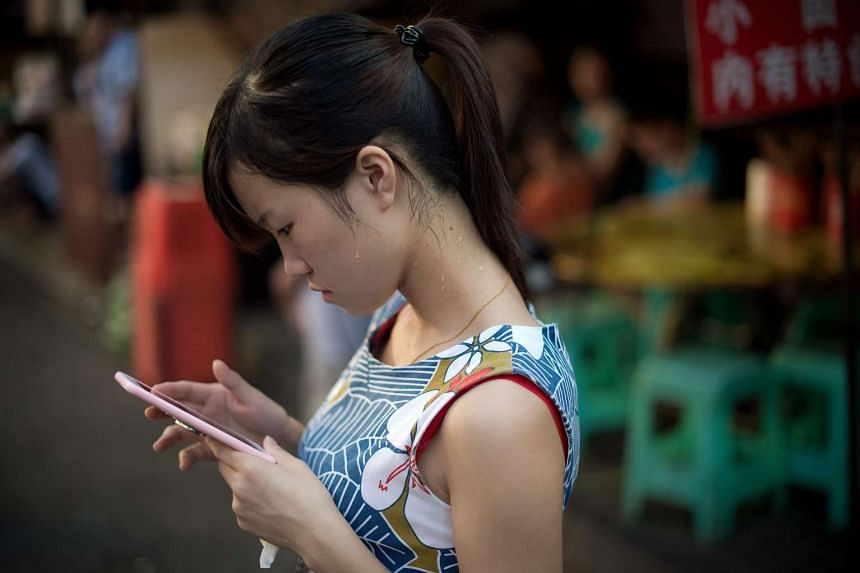 A young woman checks her smartphone in the Chinese city of Chongqing on Aug 24, 2016.