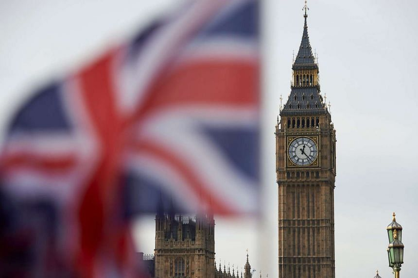 A Union flag flies in the wind in front of the Big Ben clock face in central London.